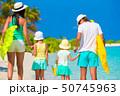 Happy family of four on white beach  50745963