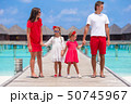 Beautiful family in red having fun on wooden jetty during summer vacation  50745967