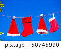 Red Santa hats and Christmas stocking hanging on tropical beach 50745990