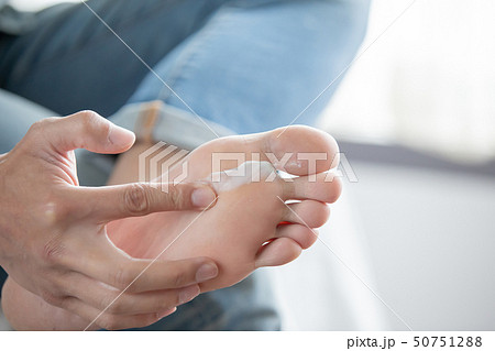 applying cream for athletes foot 50751288