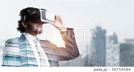 Handsome elegant businessman experiencing impressive virtual reality and business city at backdrop 50754594