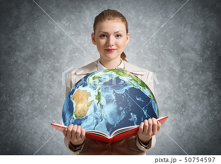 Woman showing earth globe in open book. 50754597