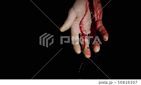 On the human hand, natural blood flows down against a dark background 50816307