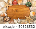 Top view. Oval wooden board lies in the sand among 50828532