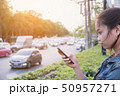 Woman using mobile phone beside road 50957271