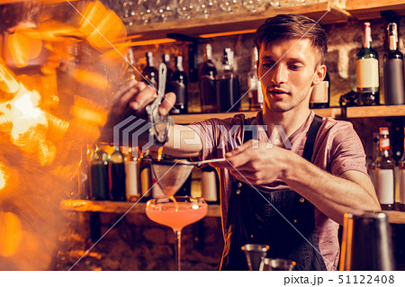 Barman pouring juice thorough sieve while making cocktail 51122408