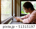 Woman using smart phone on wooden table 51315197