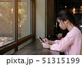 Woman using smart phone on wooden table 51315199