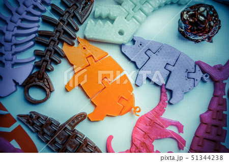 Many bright multi-colored objects printed on 3d printer lie on flat surface 51344238