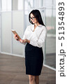 Attractive young woman wearing glasses and reading her touchscreen tablet while standing inside 51354893