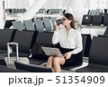 Young businesswoman in the airport, using laptop and drinking coffee, travel, business trip and 51354909