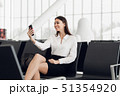 Young business woman at international airport, making selfie with mobile phone and waiting for her 51354920