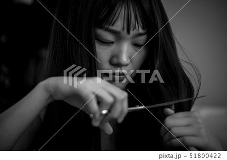 泣きながら髪を切る女性 51800422