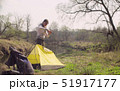 Woman putting up a tourist tent in the forest 51917177