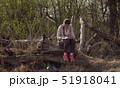 Woman sitting on a big fallen tree and writing in a diary 51918041