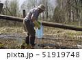 Senior woman volunteer collecting garbage in pond 51919748