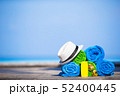 Beach and summer vacation accessories concept - close-up of colorful towels, hat, swimming goggles 52400445