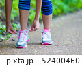 Close-up on shoe of athlete runner woman feet running on road  52400460
