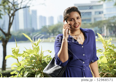 Woman talking on mobile phone outdoors 52968571