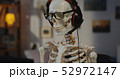 Skeleton with headphone sitting at computer 52972147