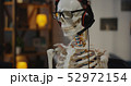 Skeleton with headphone sitting at computer 52972154