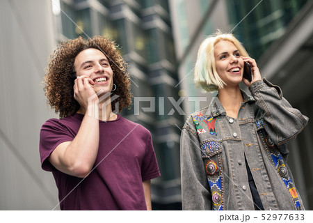 Happy couple using smartphone in urban background. 52977633