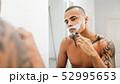Mixed race person shaving his face at morning 52995653