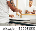Young man washing his bamboo brush in bathroom 52995655