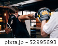 Young male boxer practicing punches in gym  52995693