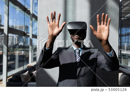 African-American businessman using virtual reality headset in office 53005126