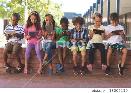 Students using digital tablet while sitting on brick wall 53005139