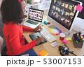 Female graphic designer using graphic tablet at desk 53007153