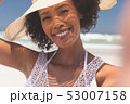 Beautiful woman with hat standing at beach on sunny day 53007158