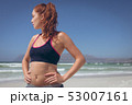 Young woman standing with hand on hip at beach  53007161