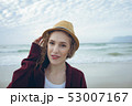 Woman looking and smiling at camera standing on the beach  53007167