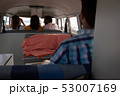 Man sitting in back of camper van while his friends are sitting in front seats 53007169