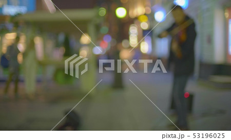 Unknown street musician plays electric violin in illuminated pedestrian area in the evening 53196025