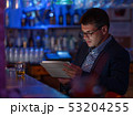 Businessman with tablet pc and whisky at the bar counter 53204255