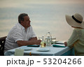 Romantic evening for mature couple in the seafront restaurant 53204266