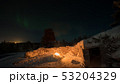 Warm light of the fire and polar lights in night sky 53204329