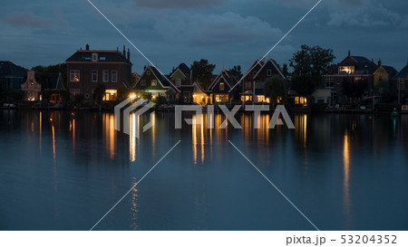Waterside Dutch village with lights reflection on water at night 53204352