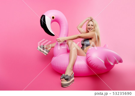 Photo of blonde in bathing suit and in pink glasses sitting on inflatable flamingo on empty pink 53235690