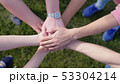Happy friends putting their hands on top of each other on the grass on the background symbolizing 53304214