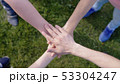 Happy friends putting their hands on top of each other on the grass on the background 53304247