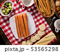 Sausage portion with baguette on table setting on checkered cloth 53565298