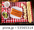 Sausage portion with baguette on table setting on checkered cloth 53565314