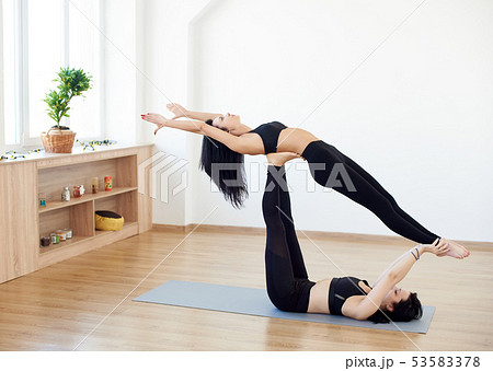 two young women doing advanced yoga practicingの写真素材