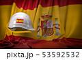 White hard hat laying over spanish  flag. 53592532