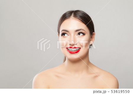 Happy young woman in braces on teeth smiling  53619550