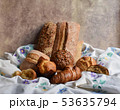 Different types of baking still life. Buns croissants, muffins and loaves, bread patties on textile 53635794